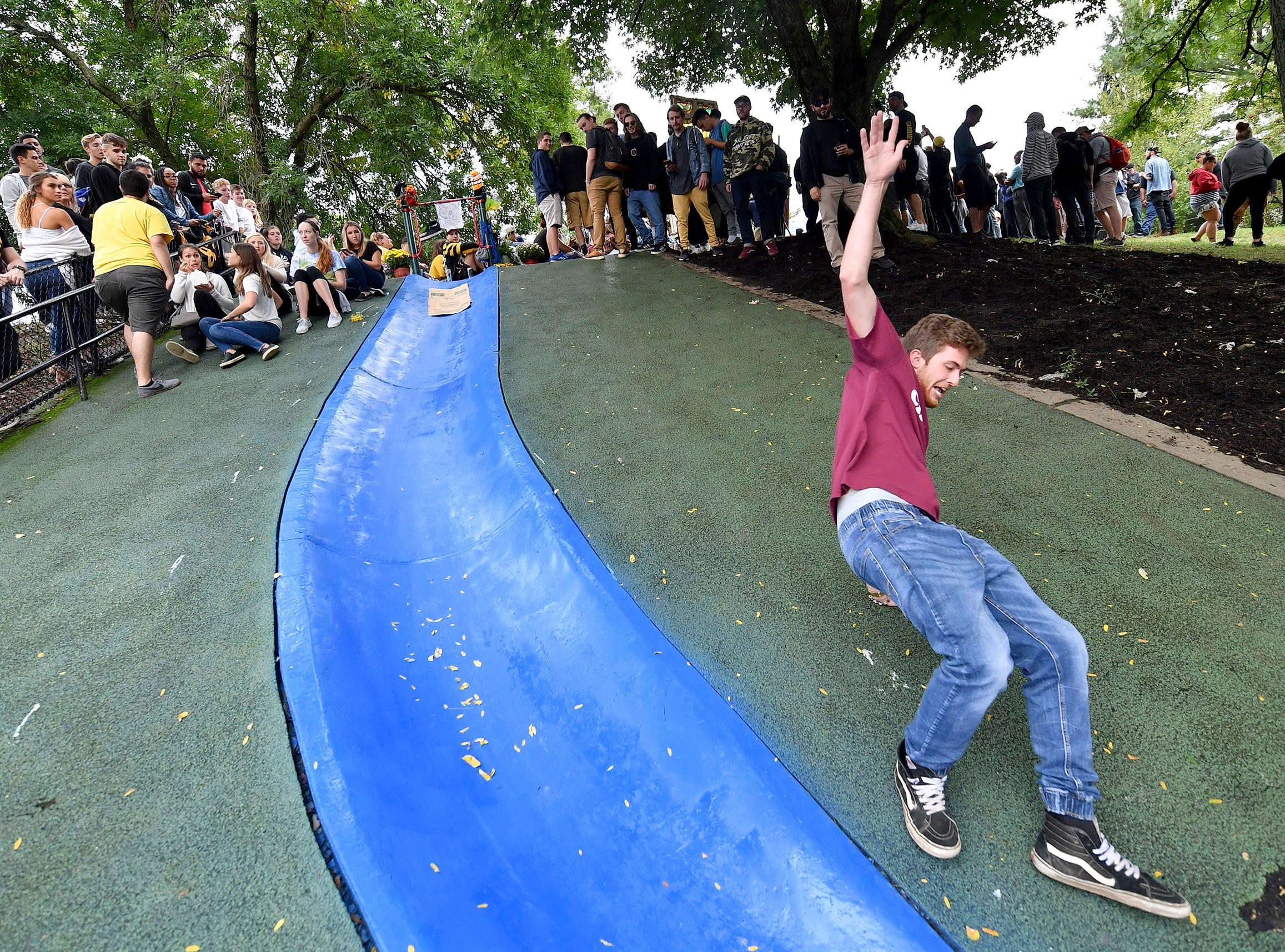 Brandon Porterfield, 21, of Mt. Pleasant, Pa. takes a slide during a vigil for rapper Mac Miller Tuesday, Sept. 11, 2018 at Blue Slide Park in Pittsburgh. Miller's debut studio album was named Blue Slide Park. (Matt Freed/Post-Gazette via AP) ORG XMIT: PAPIT103