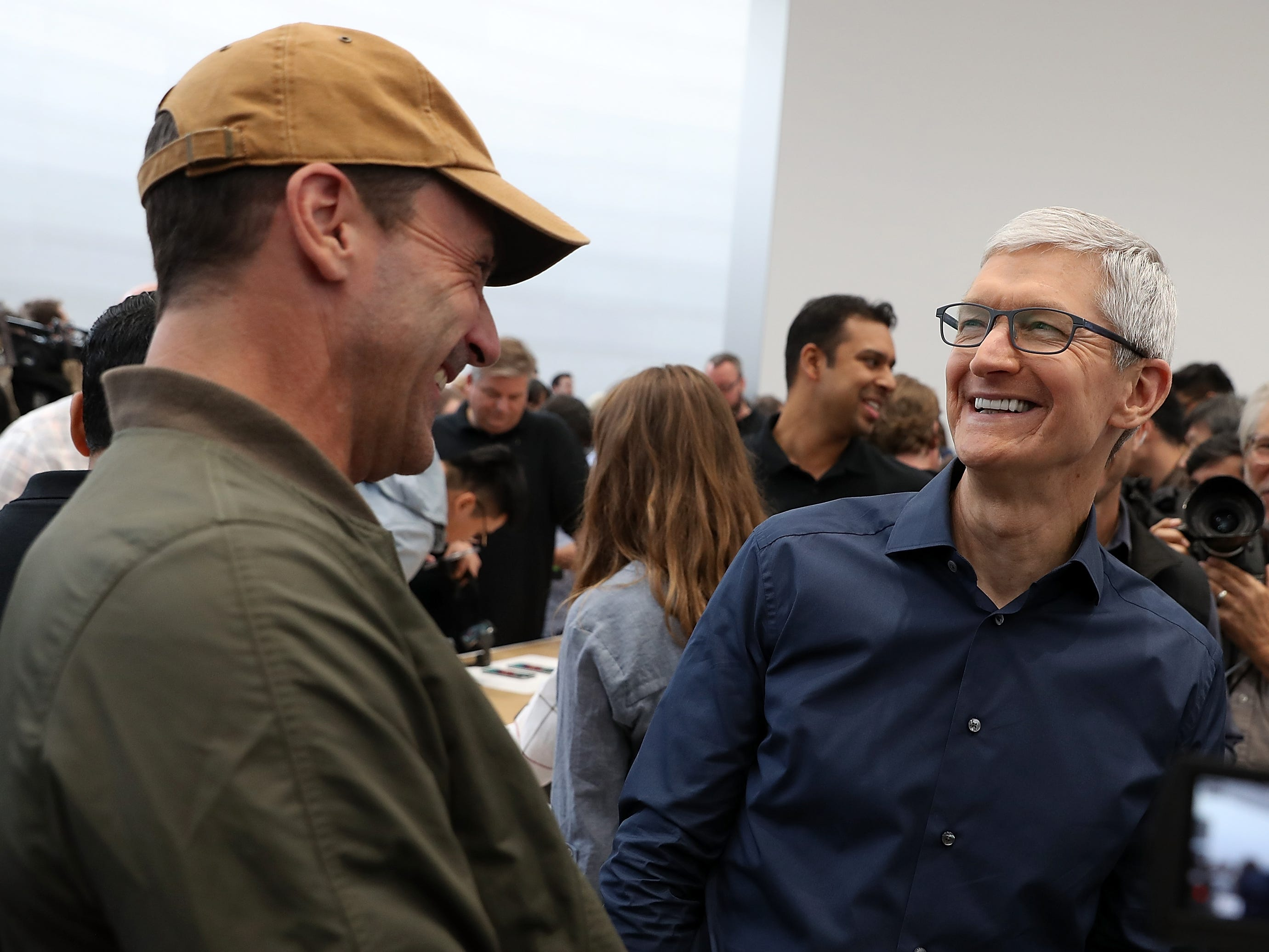 Apple CEO Tim Cook, right, laughs with actor Jon Hamm during an Apple special event at the Steve Jobs Theatre on Sept. 12, 2018, in Cupertino, Calif.