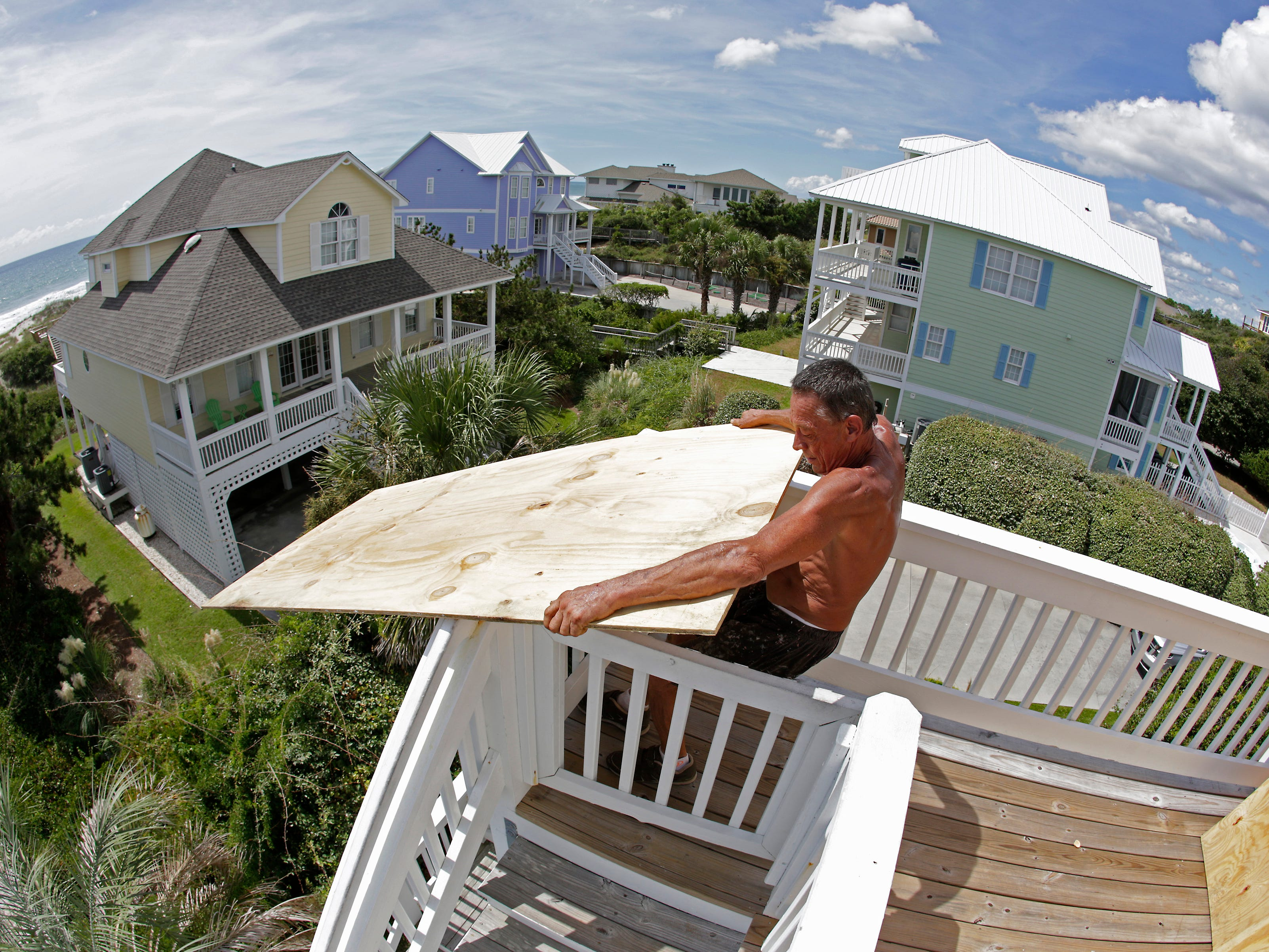 Tim Avery pulls boards to the third story of a home as he prepares for Hurricane Florence at a home in Emerald Isle N.C., Wednesday, Sept. 12, 2018.