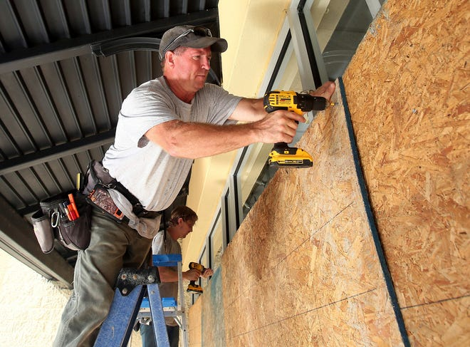 Michael Waldo, top, owner of Waldo the Framer Construction, and Robert McKeehan cover the storefront windows of Catherine's Plus Sizes with plywood Wednesday in Rocky Mount, North Carolina, in preparation for Hurricane Florence.