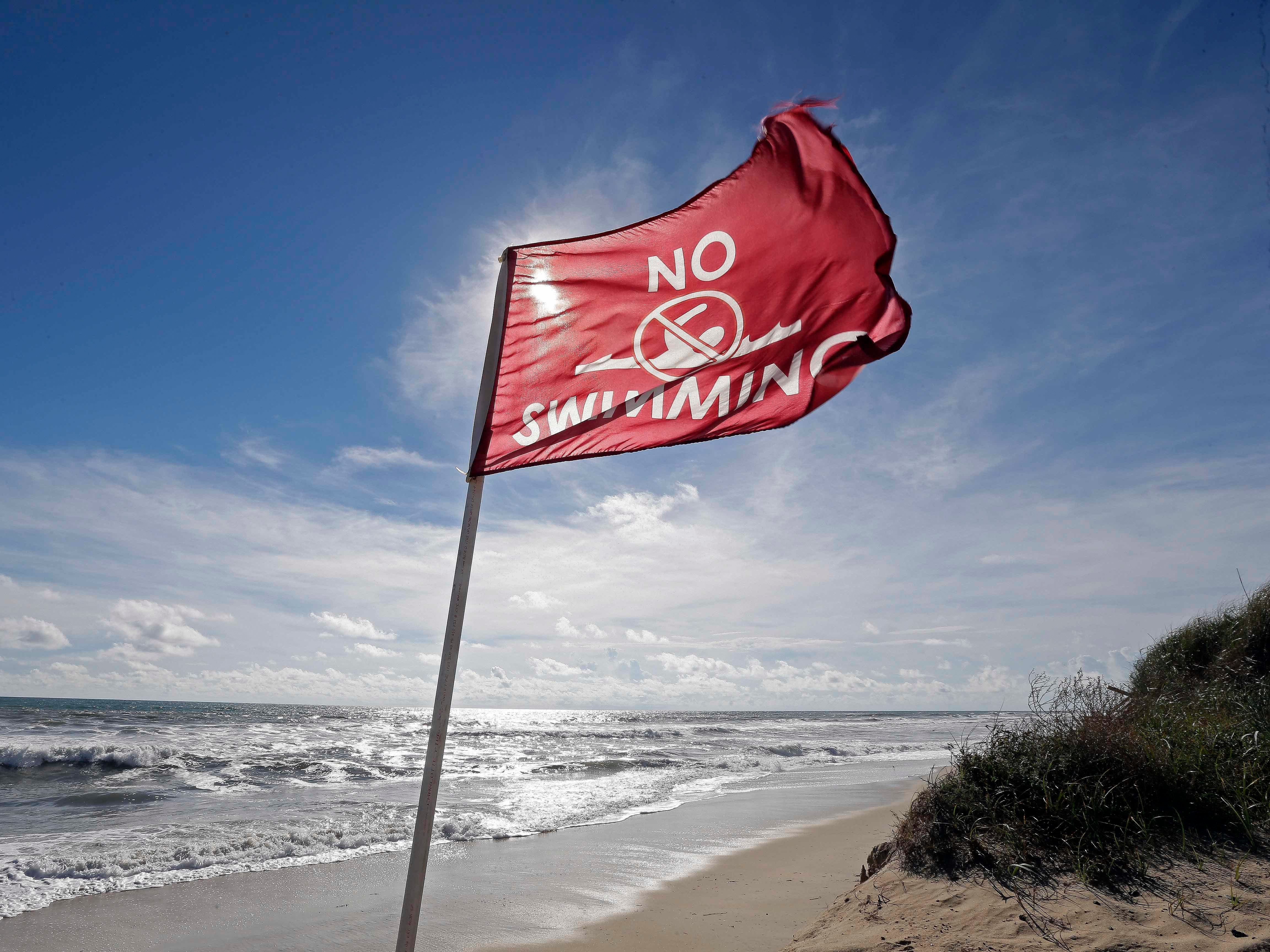 "A warning flag flies in the gusty wind near Nags Head, N.C., Wednesday, Sept. 12, 2018 as Hurricane Florence approaches the coast of the Carolinas. The National Weather Service says Florence ""will likely be the storm of a lifetime for portions of the Carolina coast."""