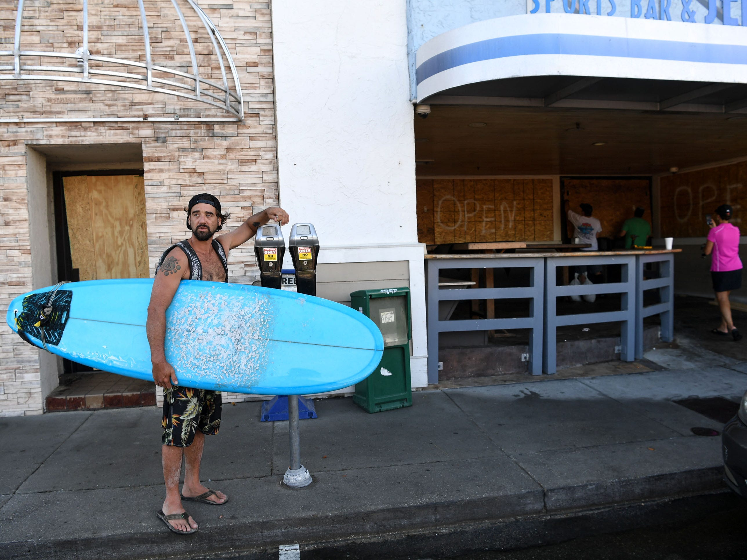 James Waters of Wilmington, N.C., finishes surfing and stopped by to see his friends boarding up Jerry Allen's Grill at Wrightsville Beach in Wilmington, N.C., Sept. 12, 2018.