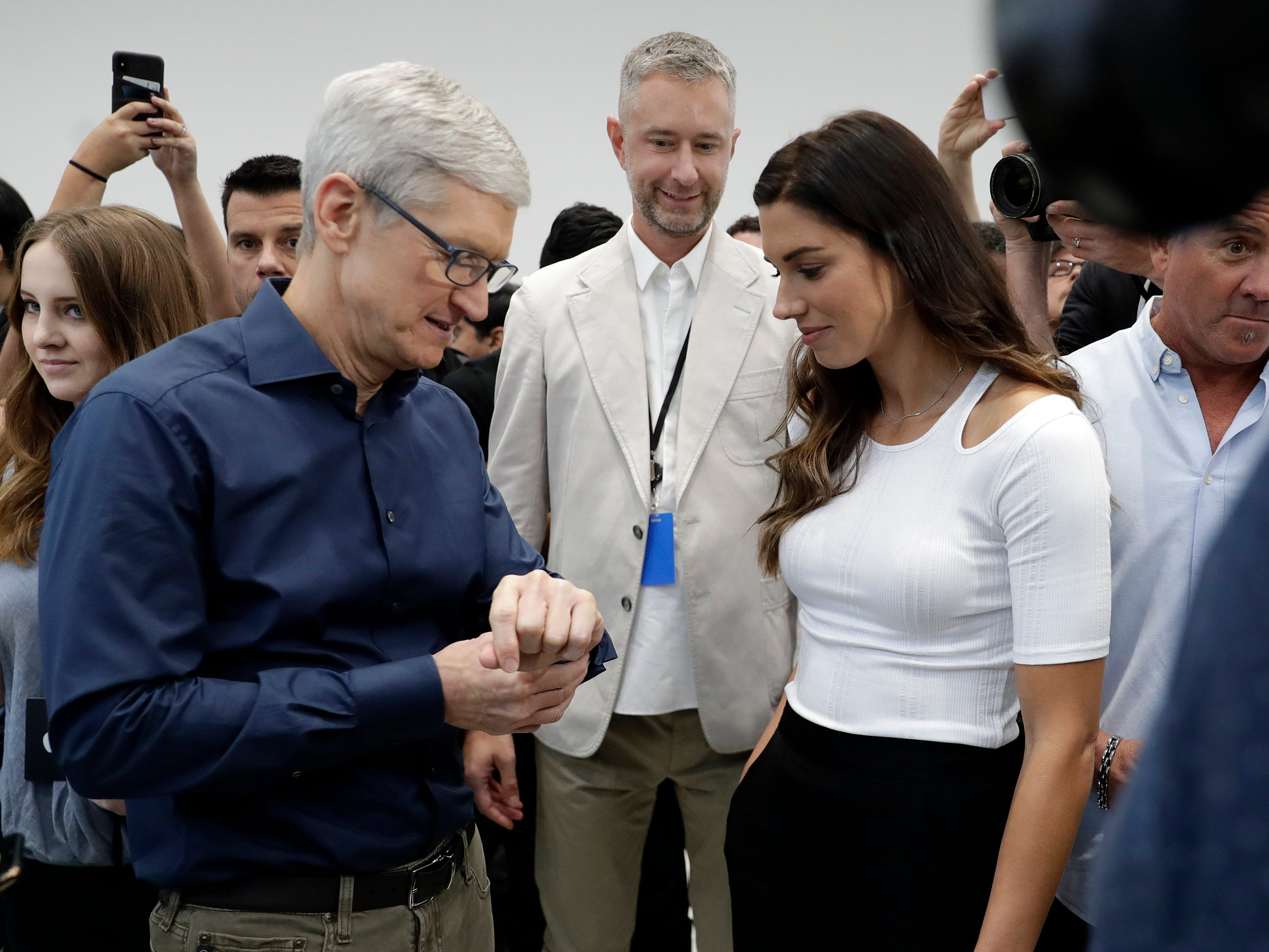Apple CEO Tim Cook, left and soccer player Alex Morgan discuss the new Apple Watch 4 at the Steve Jobs Theater during an event to announce new products Wednesday, Sept. 12, 2018, in Cupertino, Calif.