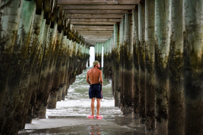 Kamil Korzec walks under the Second Avenue Pier in Myrtle Beach, S.C. on Sept. 12, 2018 days before Hurricane Florence is expected to hit the coast of North and South Carolina.