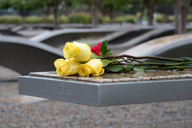 Flowers for one of the fallen sit on the National 9/11 Pentagon Memorial in Arlington, Va. on Sept. 11, 2018.