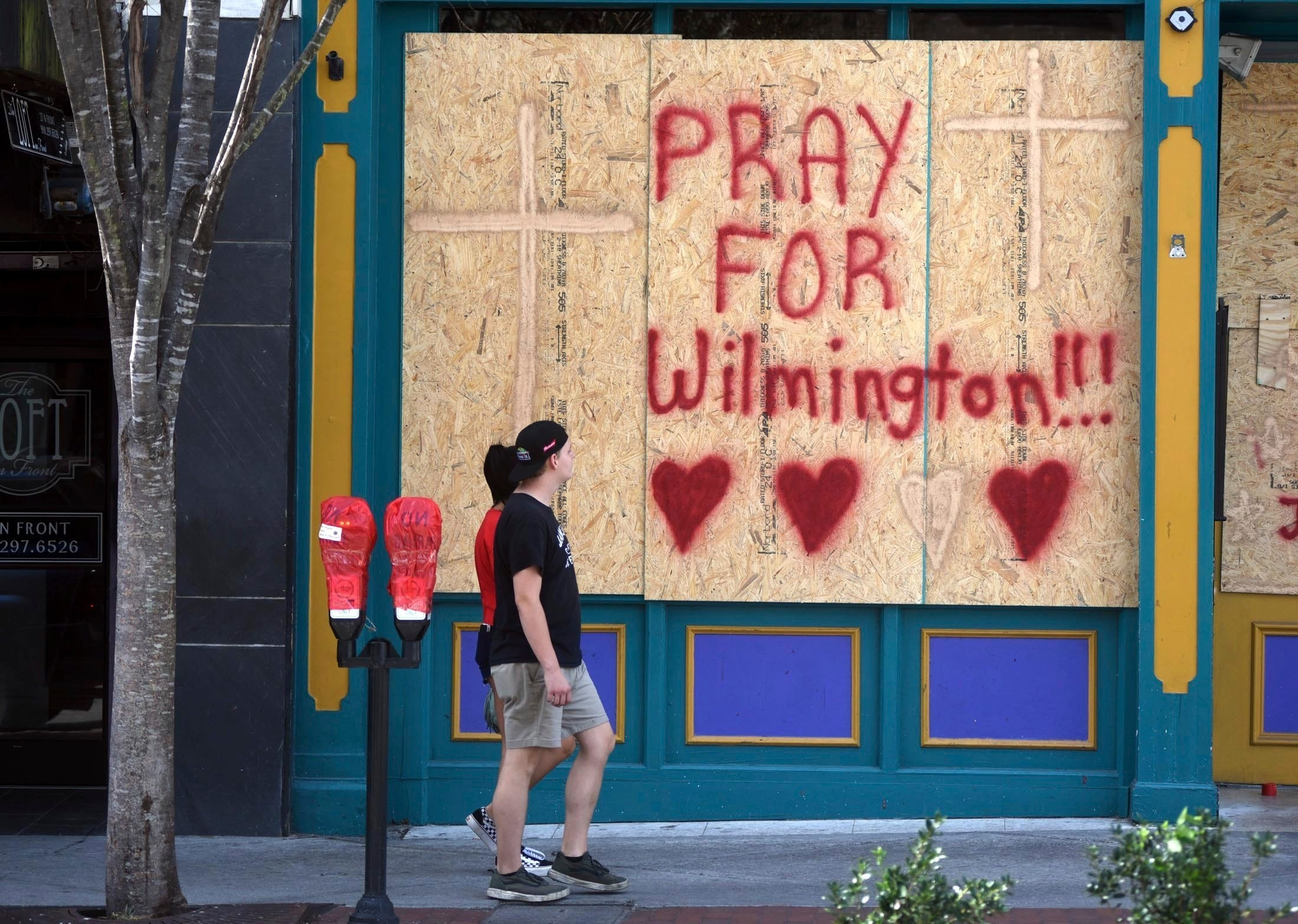 People walk by the boarded up front windows of Bourbon Street in preparation for Hurricane Florence in Wilmington, N.C., Wednesday, Sept. 12, 2018. The effects of Hurricane Florence in Southeastern North Carolina are expected to begin Thursday.