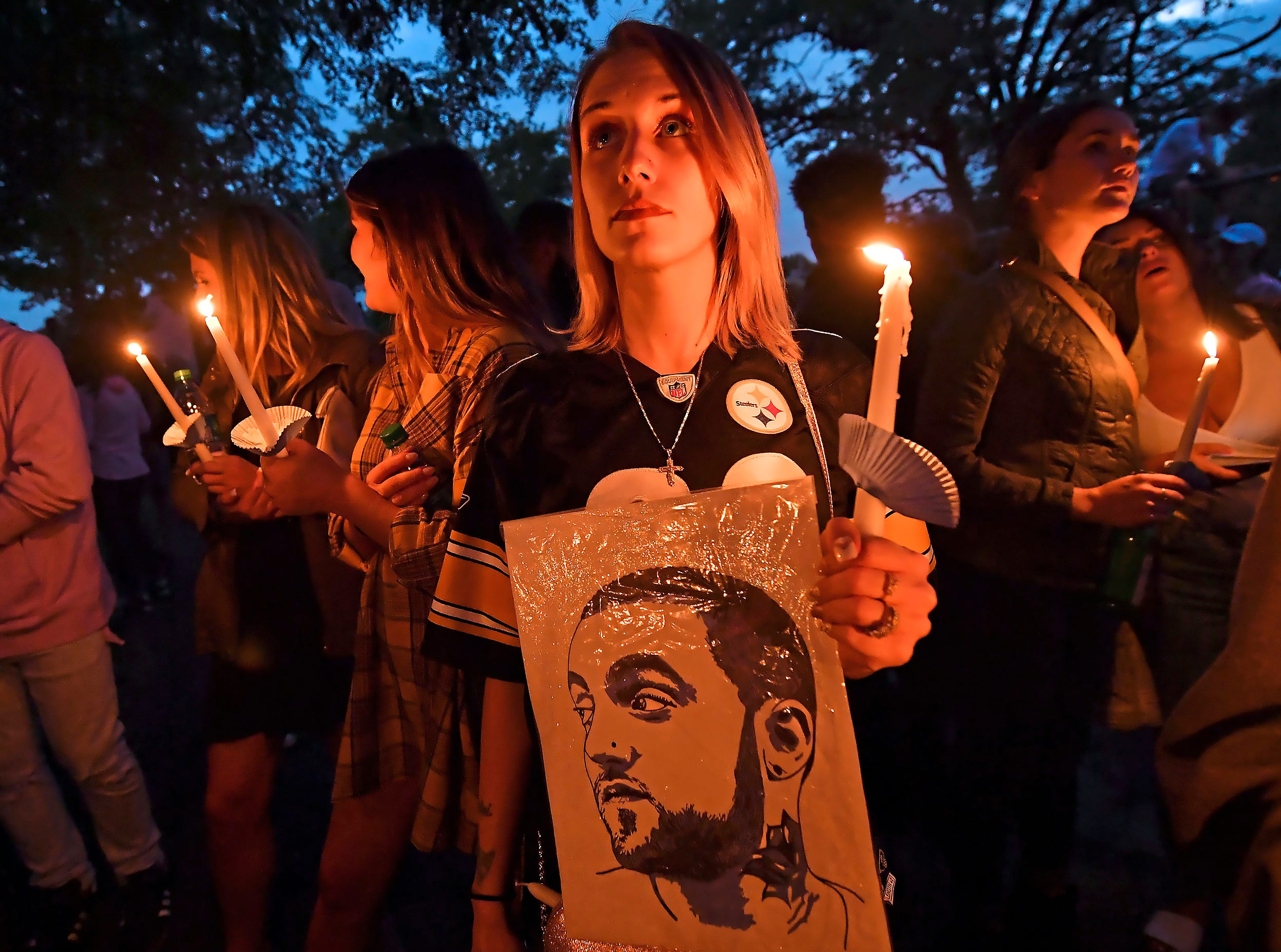 Andrea Grimm, 30, of the North Side neighborhood in Pittsburgh, holds a candle during a vigil for rapper Mac Miller Tuesday, Sept. 11, 2018, at Blue Slide Park in Pittsburgh, Pa. Blue Slide Park was the name of his debut studio album. He died last week in California. (Matt Freed/Post-Gazette via AP) ORG XMIT: PAPIT101