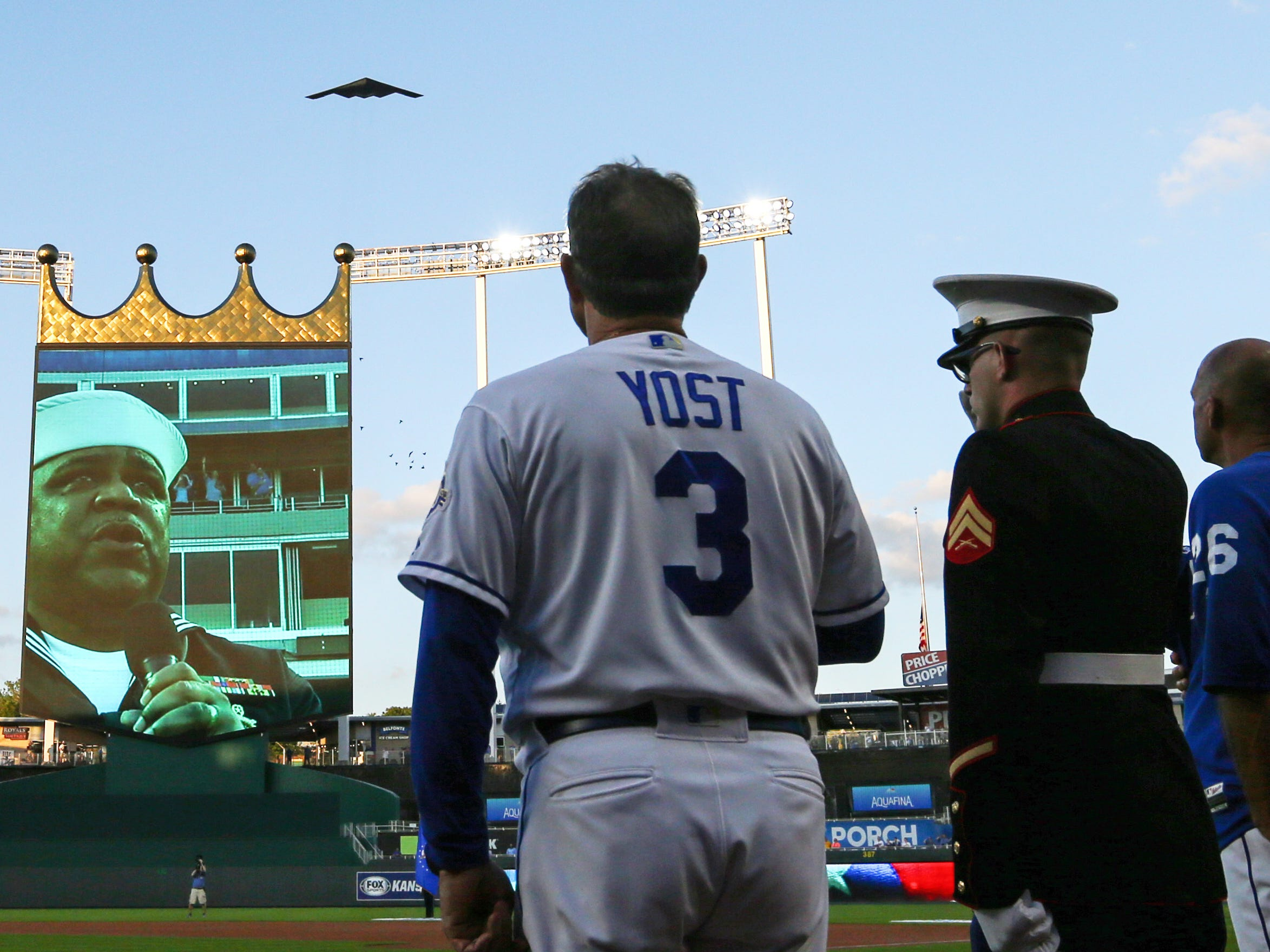 Kansas City Royals manager Ned Yost observes the national anthem alongside service members as a B-2 bomber flies over to honor those lost in the attacks of September 11, 2001.