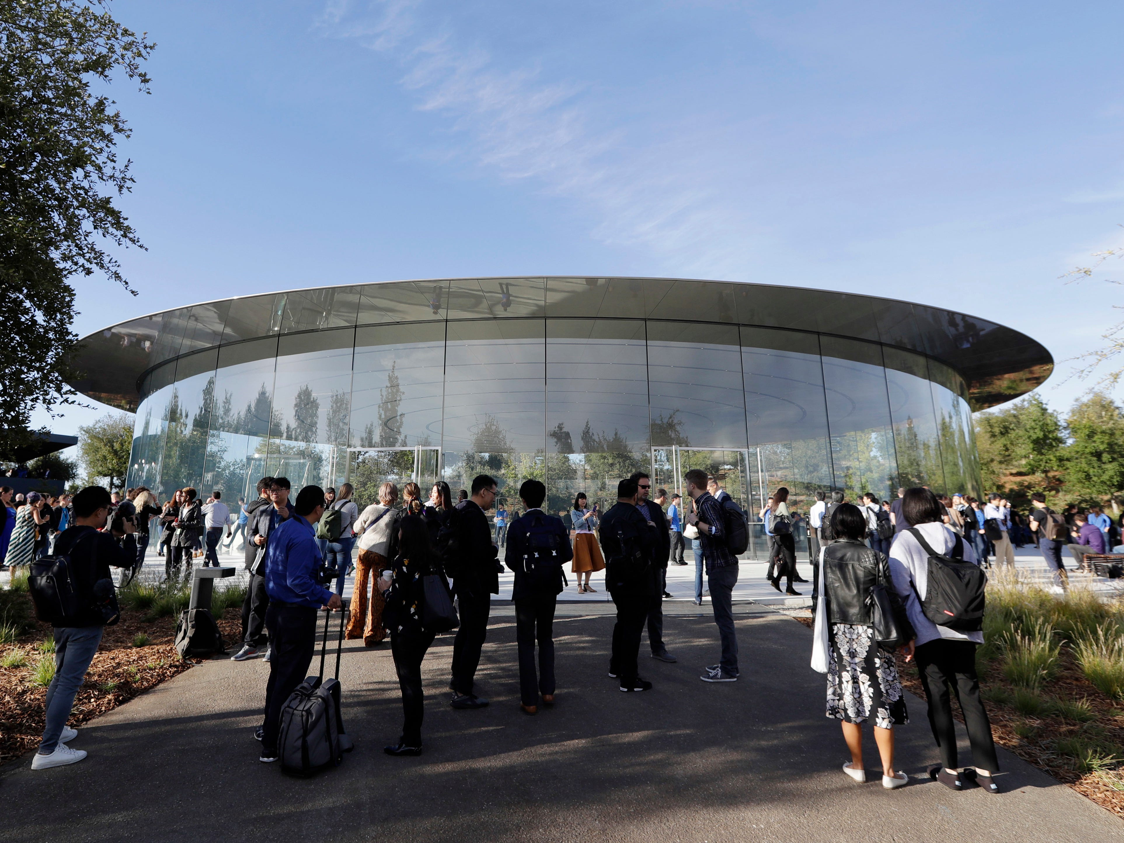People stand outside of the Steve Jobs Theater before an event to announce new Apple products Wednesday, Sept. 12, 2018, in Cupertino, Calif.