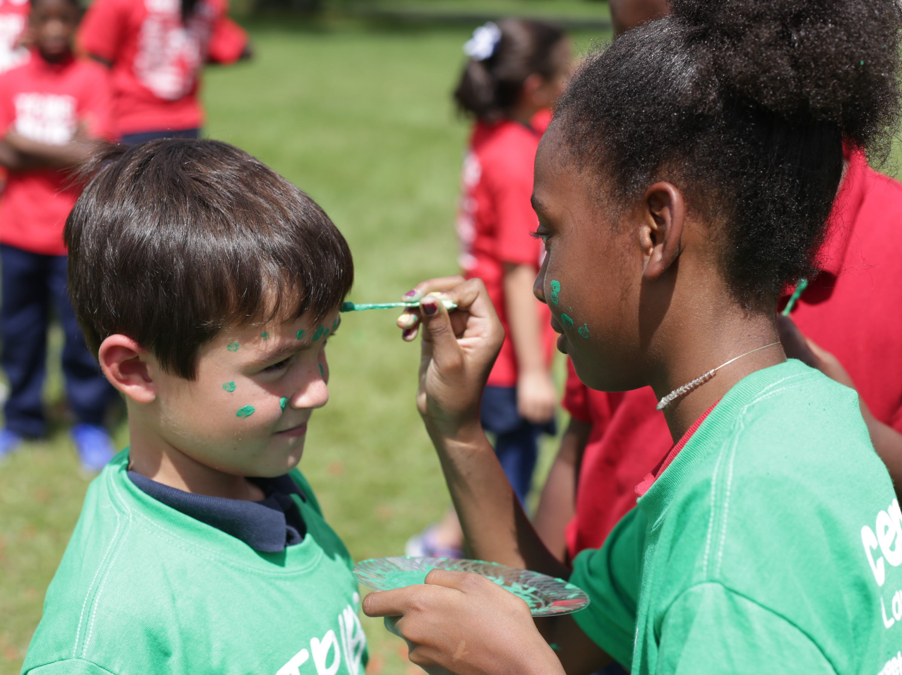 Third-graders Brody Perkins and Mi'Kaylah Guynn sport green face paint representing their tribe at Cherokee Elementary. The school randomly assigned students to tribes at a kick-off Thursday. The tribes also include teachers and staff and are meant to foster community within the school.