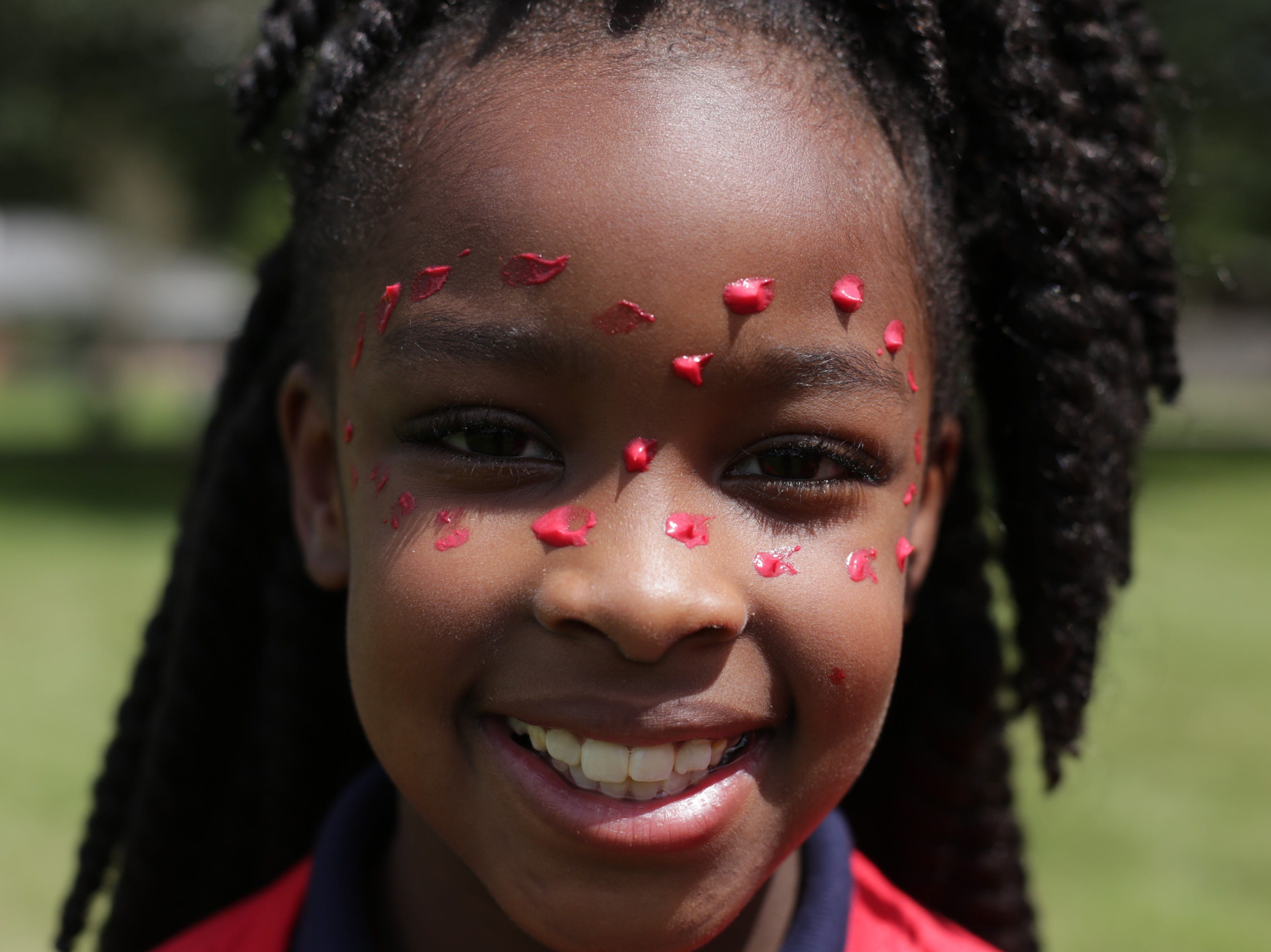 Third-grader Me'Liyah Branch sports red face paint representing her tribe at Cherokee Elementary. The school randomly assigned students to tribes at a kick-off Thursday. The tribes also include teachers and staff and are meant to foster community within the school.