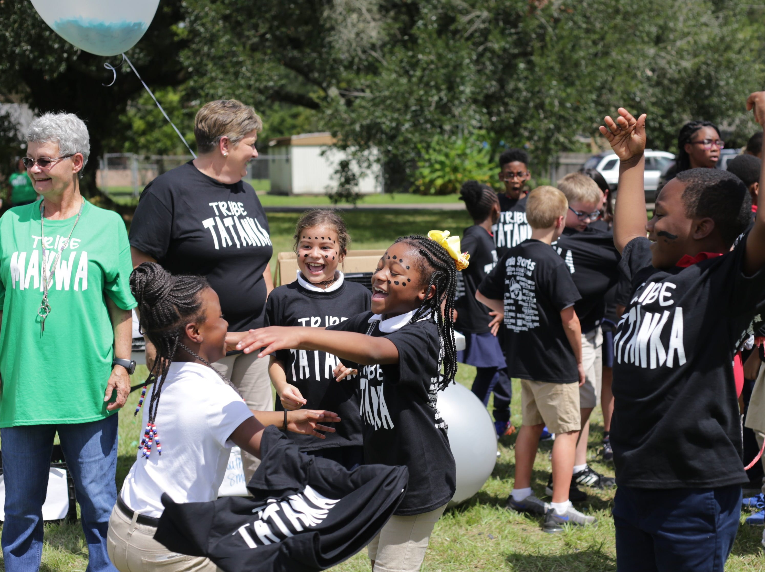 (From left) Paraprofessionals Marlene McCauley and Linda Watts along with third-graders Ja'Niya Haney, Valaya Clark, Madison Waldon and Brandon Gilbert celebrate at Cherokee Elementary's tribe kick-off Thursday. The school randomly assigned students, teachers and staff to tribes this year to help foster community.