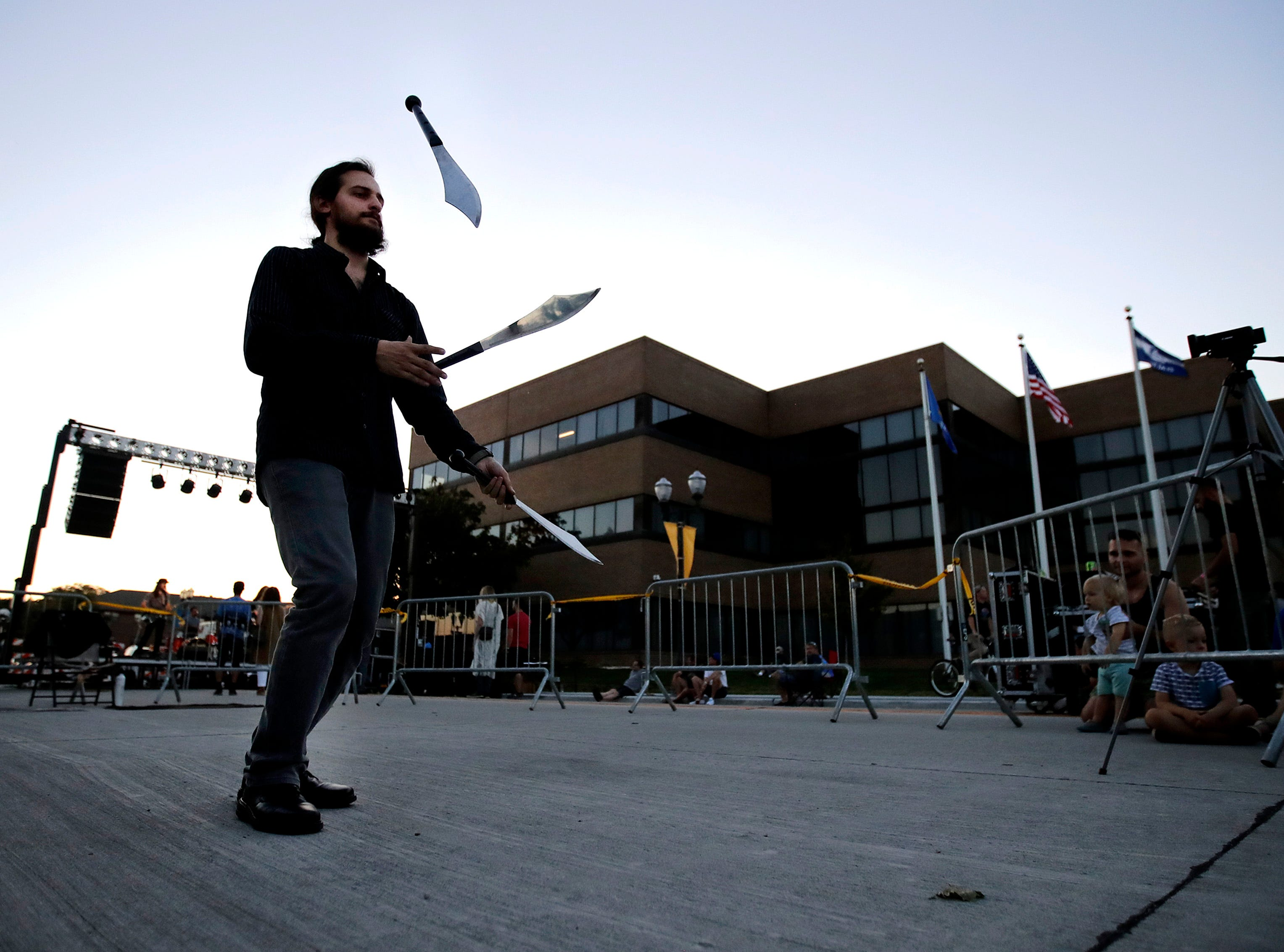 Kyle Lichtenberg, with the Fox Valley Fire and Flow Collective, juggles knives during Bazaar After Dark Wednesday, Sept. 12, 2018, in Menasha, Wis.Danny Damiani/USA TODAY NETWORK-Wisconsin