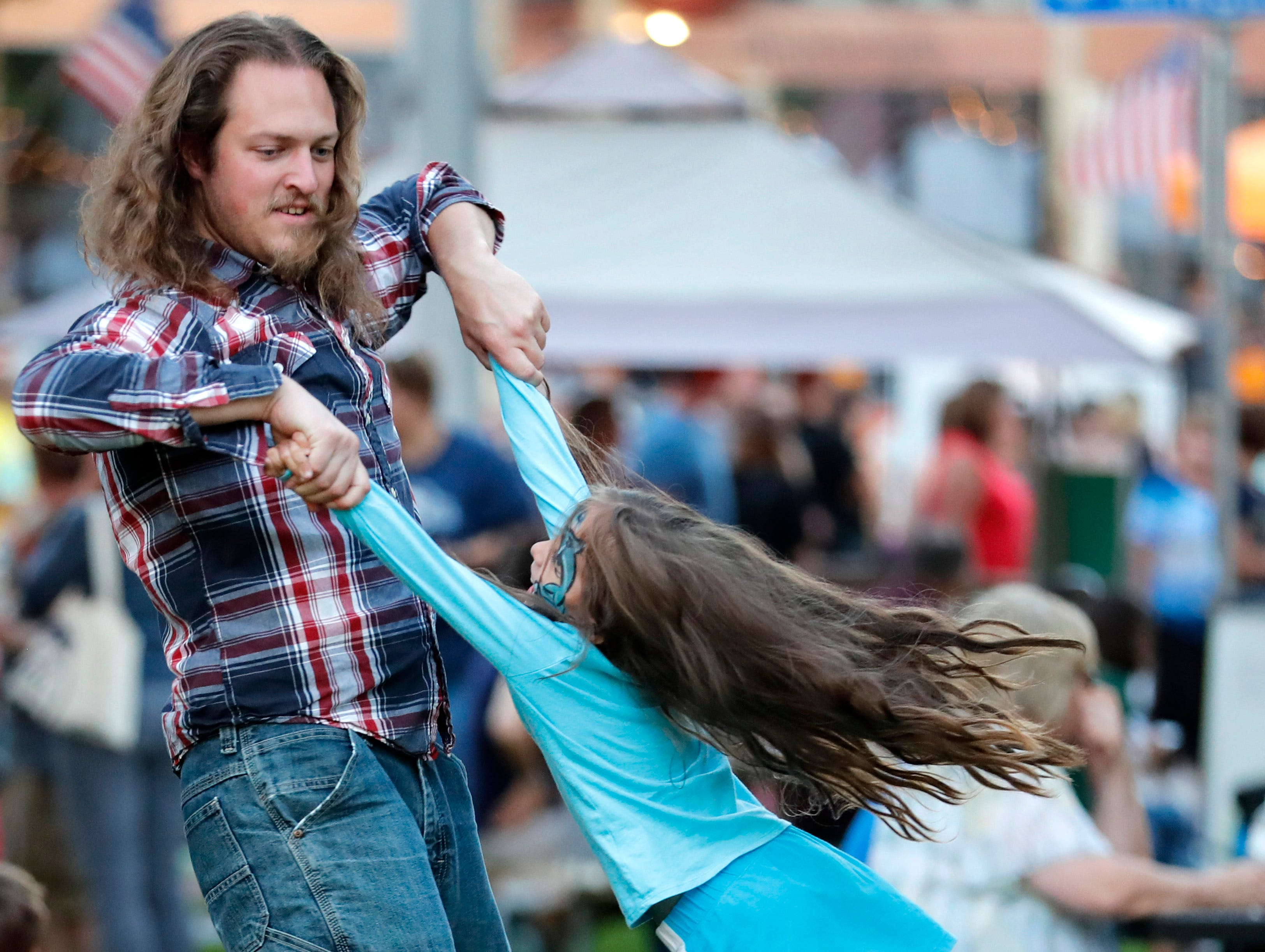 David Mclean, of Neenah, spins Madelyn Hess, 6, while dancing during Bazaar After Dark Wednesday, Sept. 12, 2018, in Menasha, Wis.Danny Damiani/USA TODAY NETWORK-Wisconsin