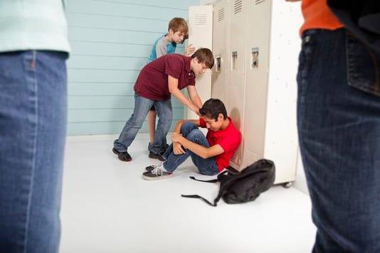 Teenage Boys Bully Classmate In School Hallway