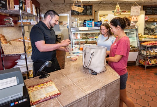 Co-owner Angelo Locicero rings up Florence Wright (right) and her daughter Emma Wright, both of Little Silver, at  Angelo's Italian Market, Little Silver.