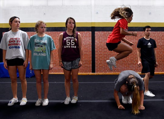 Junior Hanna Wolford leapfrogs over a fellow Abilene High cheerleader during practice Wednesday.