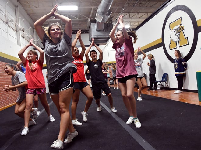 Abilene High School cheerleaders practice Wednesday. Eagles cheerleading coach Randi Odell is a 2008 Cooper High School graduate whose squad will be cheering against her alma mater during Friday's crosstown rivalry football game at Shotwell Stadium.