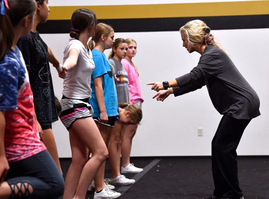 Randi Odell works with the junior varsity Eagles cheerleaders during practice Wednesday at Abilene High School.
