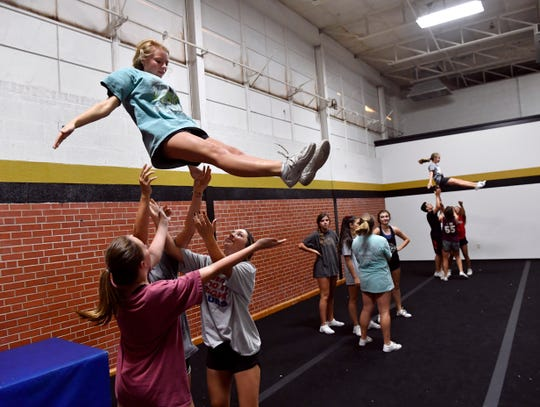 Junior Morgan Zara descends into the arms of her fellow Abilene High School cheerleaders during practice Wednesday. Eagles cheerleading coach Randi Odell is a 2008 Cooper High School graduate whose squad will be cheering against her alma mater during Friday's crosstown rivalry football game.