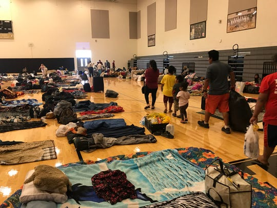 Evacuees from Hurricane Florence, including more than one hundred migrant farmworkers, prepare to seep in a high school gym in Clinton, North Carolina.