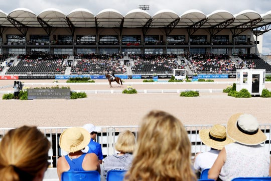 Spectators watch as Julio Mendoza, of Columbus, NC, competes for Ecuador in dressage at the World Equestrian Games in Tryon Sept. 13, 2018.