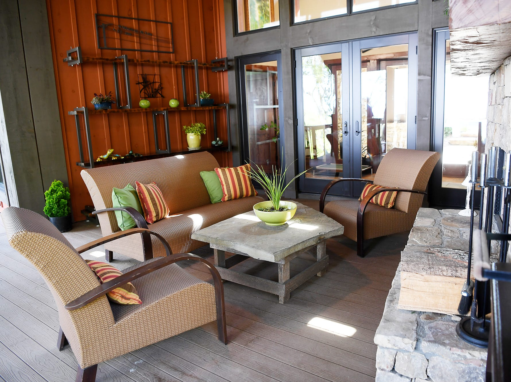 Furniture surround a fireplace on the porch of Jim and Sabrina Watson's Balsam Mountain Preserve home in Jackson County.
