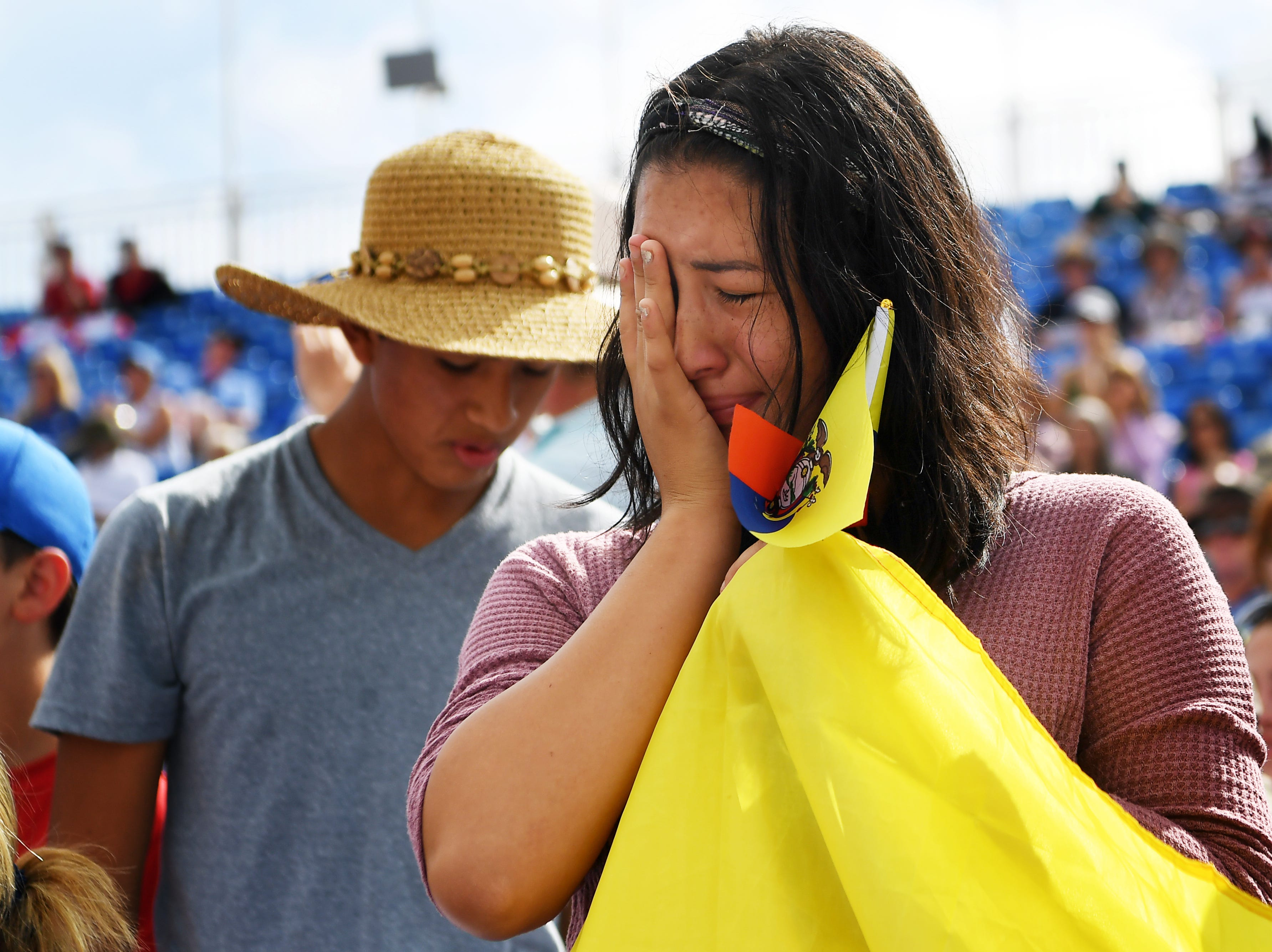 Francis Mendoza, 17, holds Ecuadorian flags and cries as her father, Julio, finishes his dressage competition at the World Equestrian Games in Tryon Sept. 13, 2018.