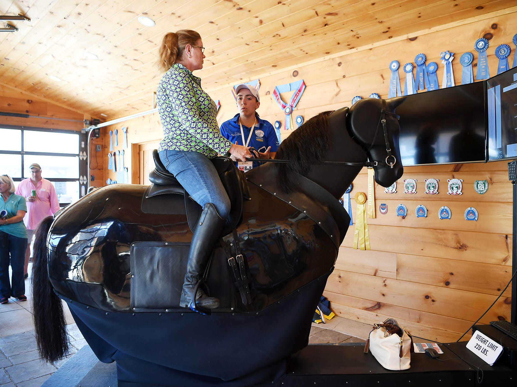 Sara Love, of New York, rides a horse simulator with help from Juliana Gutierrez, of Columbia, at the World Equestrian Games in Tryon Sept. 13, 2018.