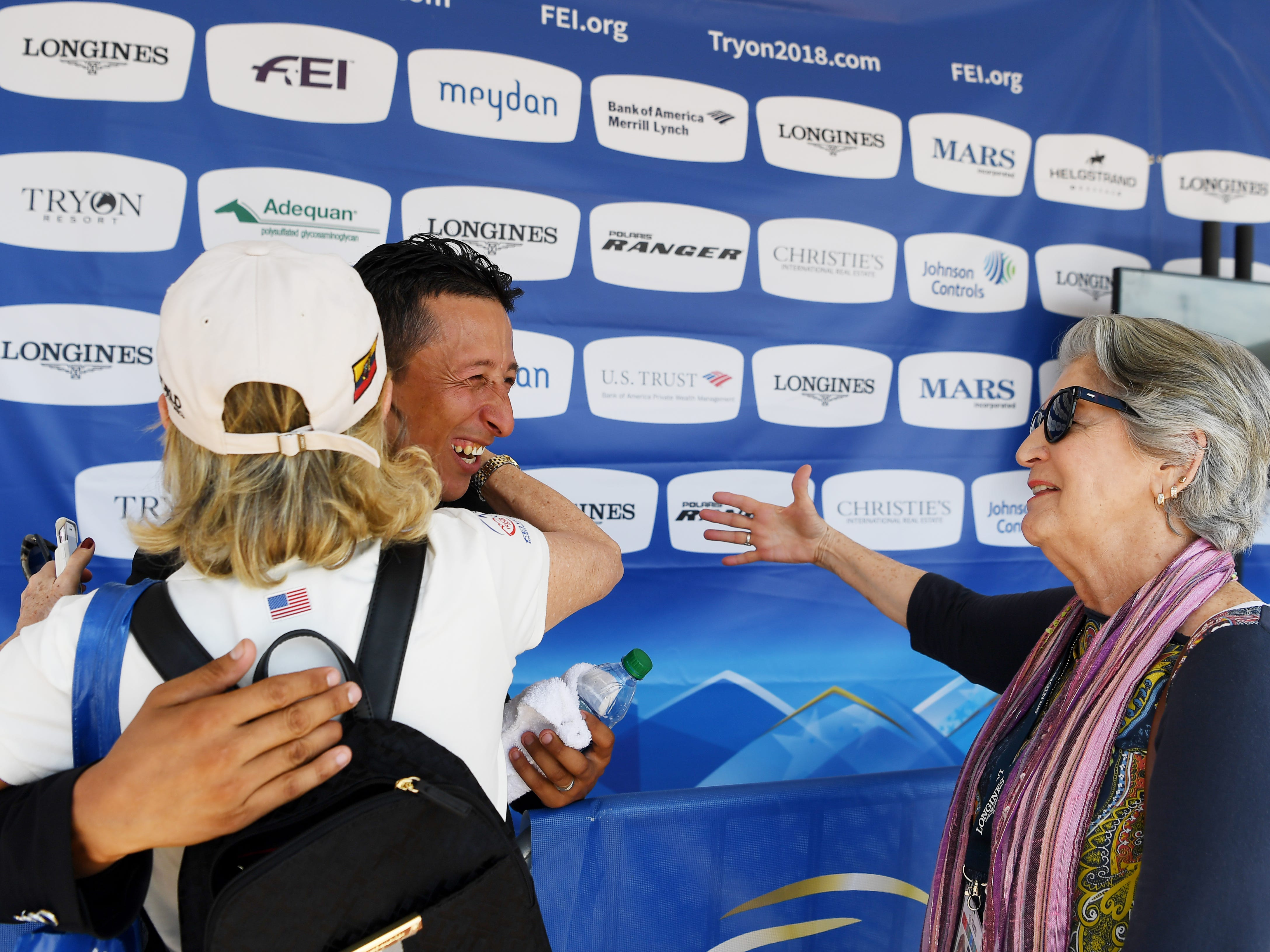 Julio Mendoza, of Columbus, NC, is congratulated by Gloria Vinueza de Cuesta, left, and Isabel Maldonada following his competition in dressage at the World Equestrian Games in Tryon Sept. 13, 2018.
