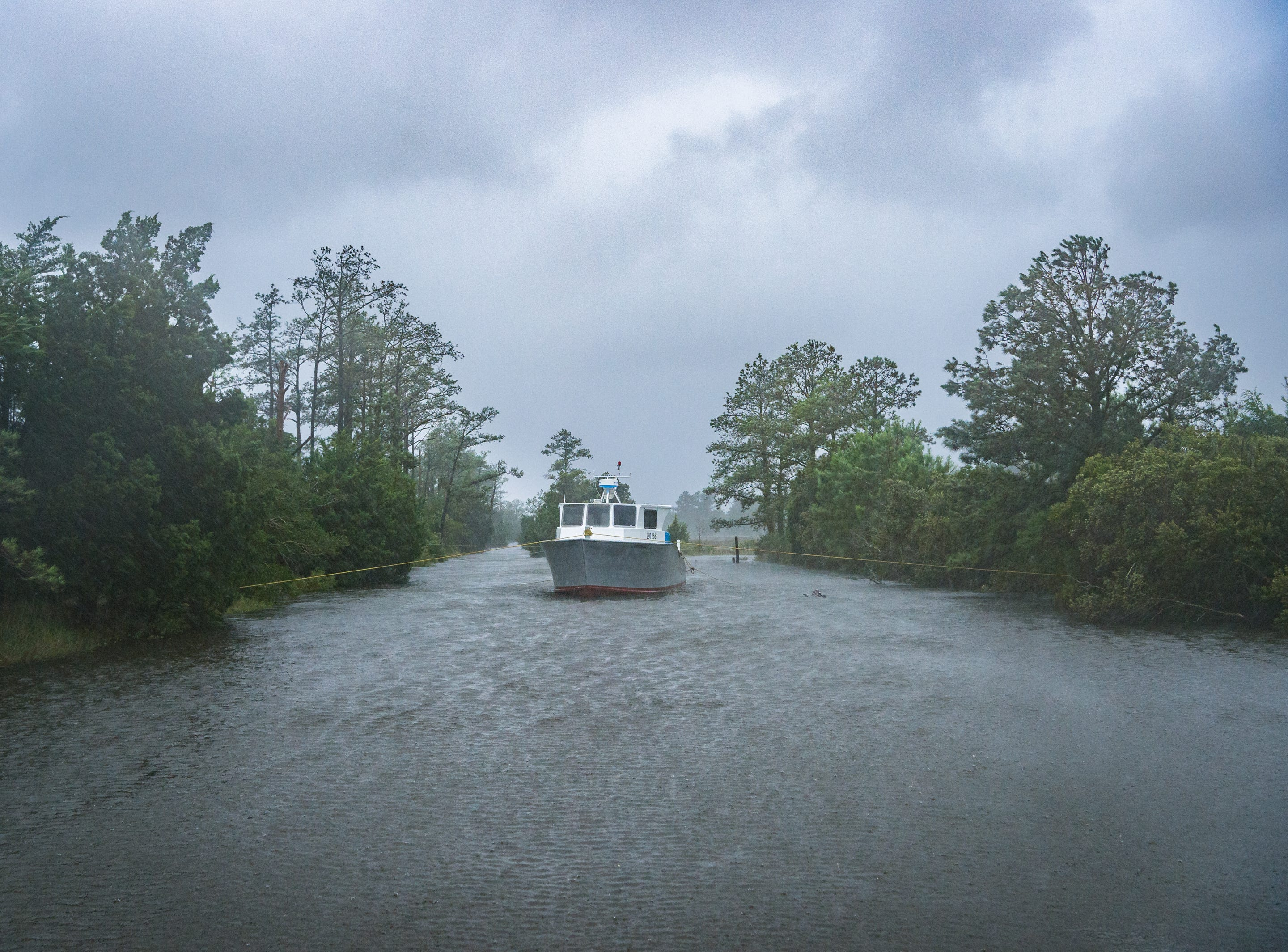 A boat sits tied up on a creek on Oyster Creek street in Swan Quarter, N.C, with heavy rain and wind increasing as Hurricane Florence nears the coastline Sept. 13, 2018.
