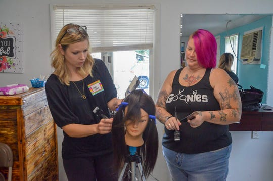 Tara Gage, a stylist from Ann Arbor, and Jennifer Hollon, owner of Jen-Nay's Hair Studio, test out balayage techniques on a mannequin's hair at a balayage workshop on Monday, Sept. 10, 2018.