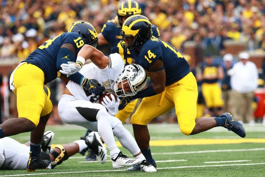 Chase Brown (28) of the Western Michigan Broncos runs the ball and is tackled by Kyle Grady (14) and Kwity Paye (19) of the Michigan Wolverines at Michigan Stadium on September 8, 2018 in Ann Arbor, Michigan.