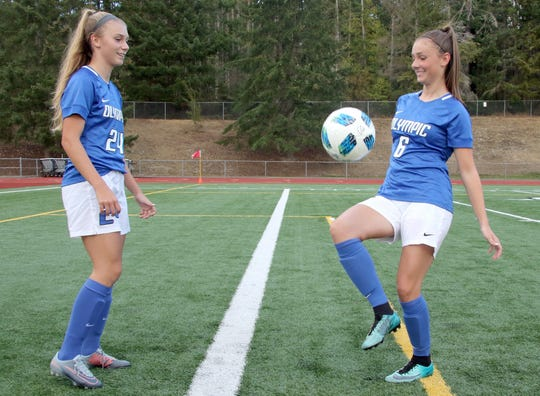 Twin sisters Hanna, left, and Sydney Troy, of Olympic High, before a recent game against North Mason at Silverdale Stadium.