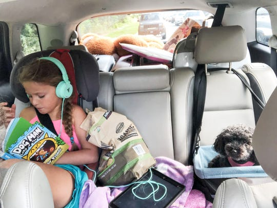 Mia,7, and family dog Coco on the trip to Florida in a photo by Kelley Esposito.  Rick and Kelly Esposito of Mount Pleasant, South Carolina, along with their daughter Mia, 7, and family dog Coco, are staying with friends in Viera after leaving their home in S.C. in the path of Hurricane Florence.