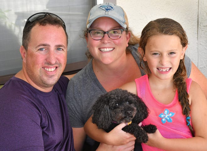"Relaxing on their ""Evacuation vacation"", as Kelley describes it. Rick and Kelly Esposito of Mount Pleasant, South Carolina, seen here with daughter Mia, 7, and family dog Coco, are staying with friends in Viera after leaving their home in S.C. in the path of Hurricane Florence."