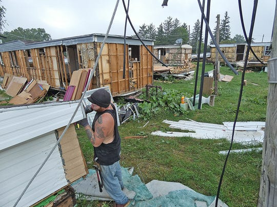 Adam Beecham salvages materials from a trailer Thursday at McFarland's Mobile Home Park on Mansfield Street on the east side of Bucyrus.