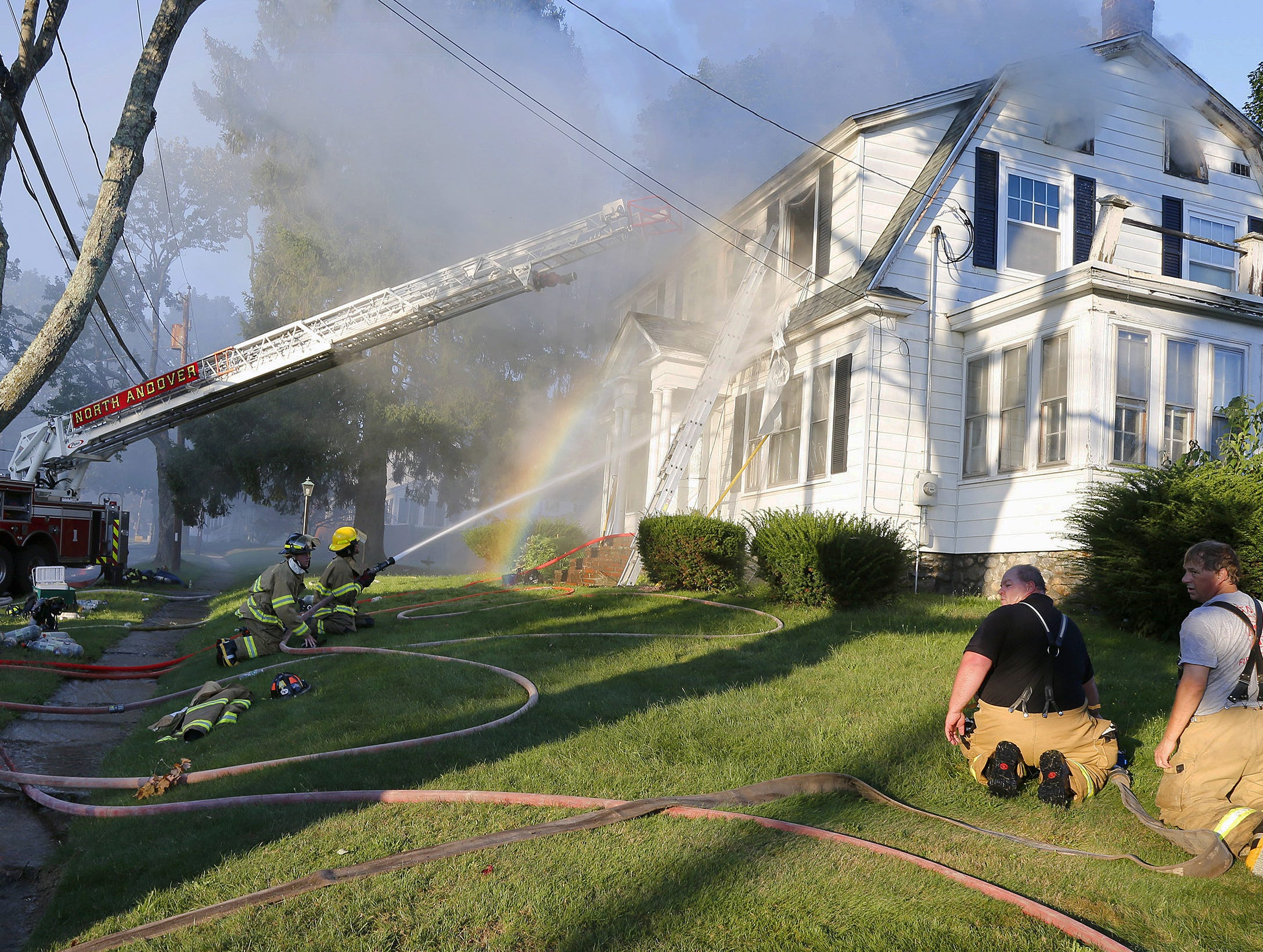 Firefighters battle a house fire, Thursday, Sept. 13, 2018, on Herrick Road in North Andover, Mass., one of multiple emergency crews responding to a series of gas explosions and fires triggered by a problem with a gas line that feeds homes in several communities north of Boston.