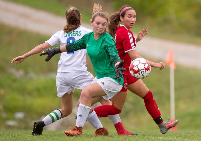Colchester's Olivia Moore, center, and Champlain Valley's Sara Kelley watch the ball bounce toward the goal — but not go in — during Wednesday's high school girls soccer game in Hinesburg on Sept. 12, 2018.