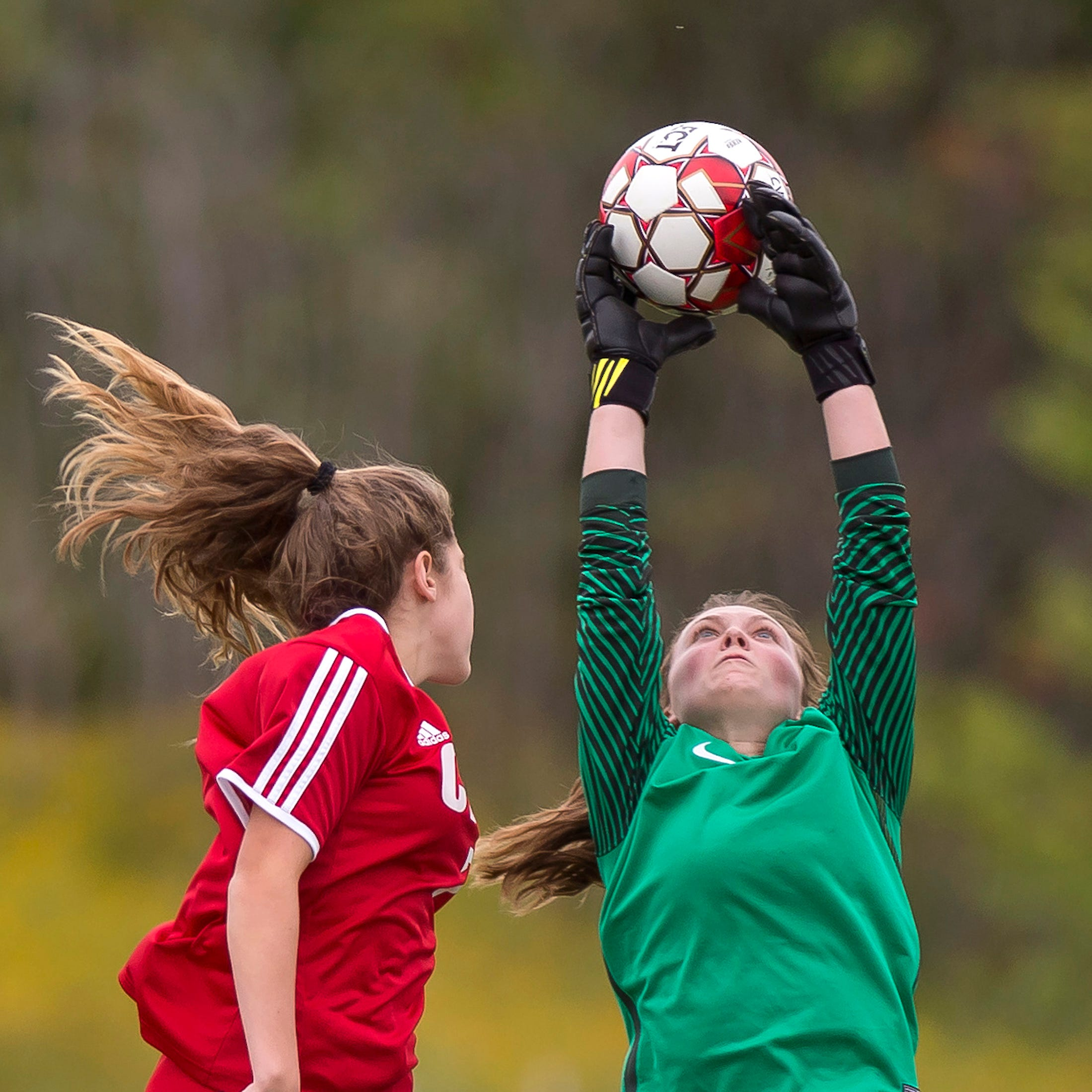 Colchester goalie Olivia Moore, right, snares a cross above the head of a Champlain Valley player during Wednesday's high school girls soccer game in Hinesburg on Sept. 12, 2018.