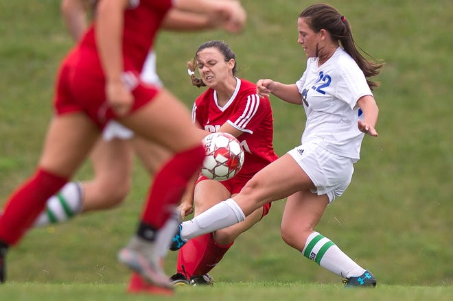Champlain Valley's Lilly Cazayoux, center, gets a cross off ahead of Colchester's Summer Hathaway during Wednesday's high school girls soccer game in Hinesburg on Sept. 12, 2018.