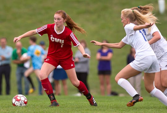 Champlain Valley's Catherine Gilwee, left, looks to elude two Colchester defenders during Wednesday's high school girls soccer game in Hinesburg on Sept. 12, 2018.