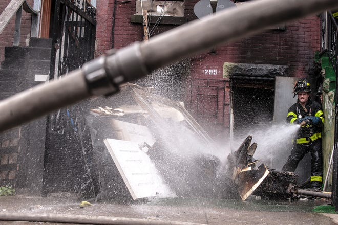 """Lloyd Mitchell's photograph of a firefighter hosing down debris is among the works included in """"On the Streets: Through the Eyes of Firefighters."""""""