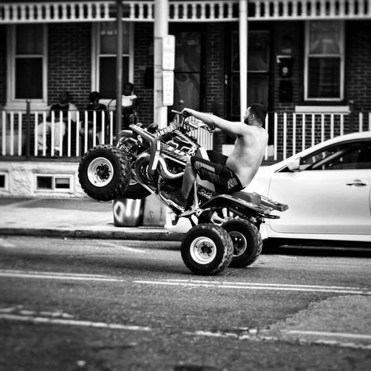 """A man rides through Camden on an ATV in this Angelo Perez photograph, part of """"On the Street: Through the Eyes of Firefighters"""" at Camden FireWorks."""