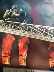 """Warren Fuchs' photograph of firefighters saving a child from a burning building is among the works included in """"On the Street: Through the Eyes of Firefighters"""" at Camden FireWorks."""