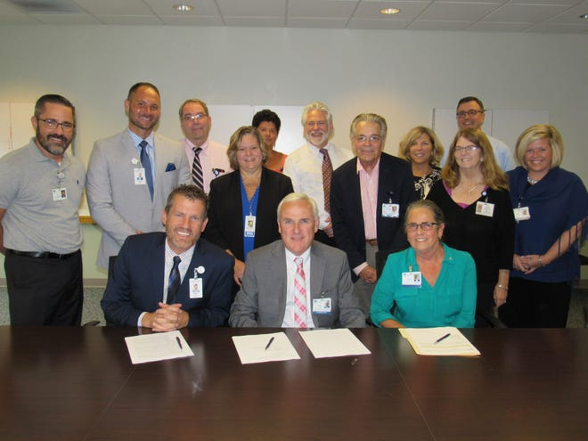 Fayette County Memorial Hospital's CEO Mike Diener, Adena Health System President & CEO Jeff Graham, and Adena Board of Trustees Chair Virginia Wettersten sign affiliation agreement between the two, independent health care providers. Members of FCMH and Adena leadership teams also pictured.