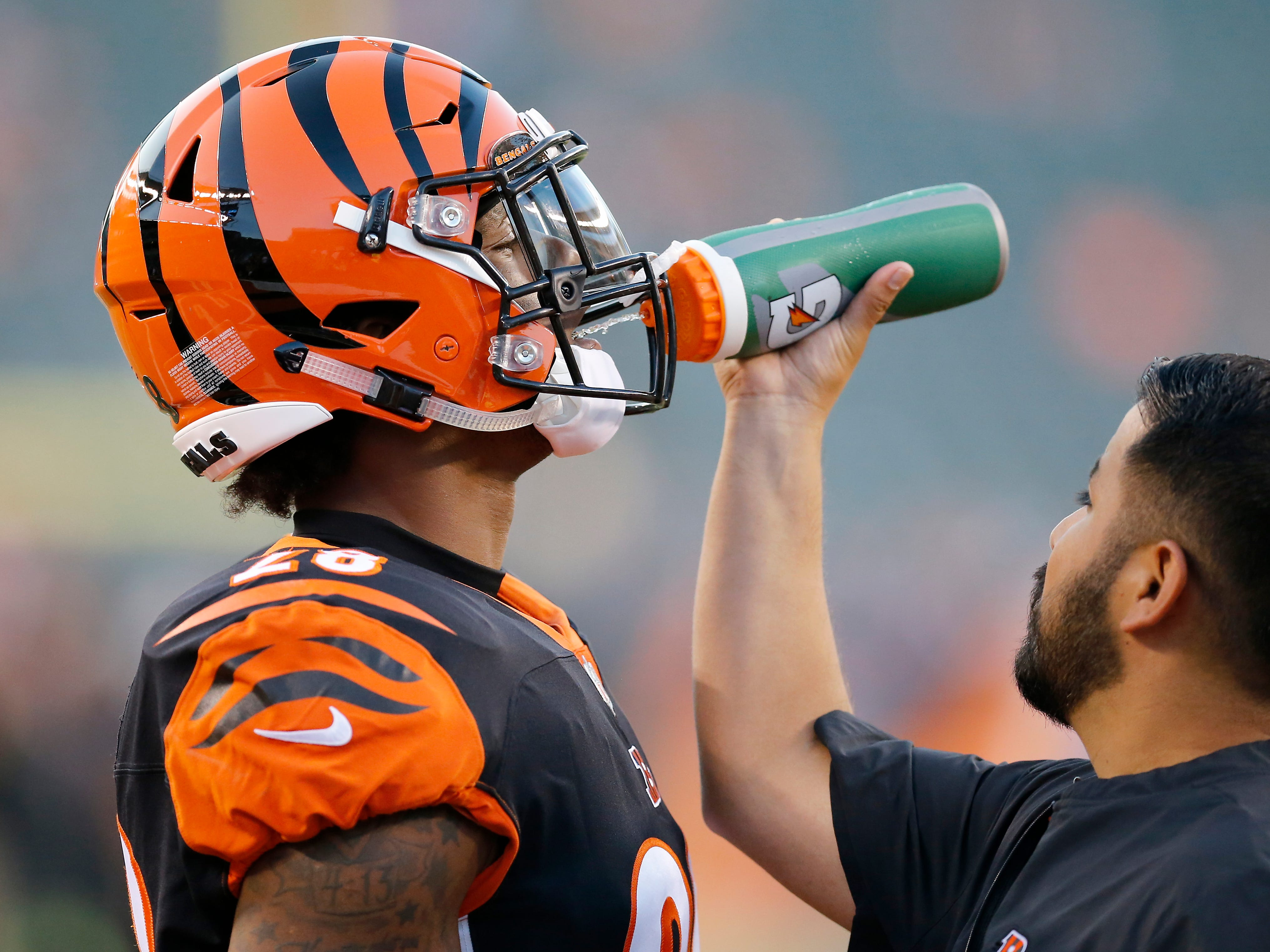 Cincinnati Bengals running back Joe Mixon (28) gets a drink during pregame warmup before the NFL Week 2 game between the Cincinnati Bengals and the Baltimore Ravens at Paul Brown Stadium in downtown Cincinnati on Thursday, Sept. 13, 2018.