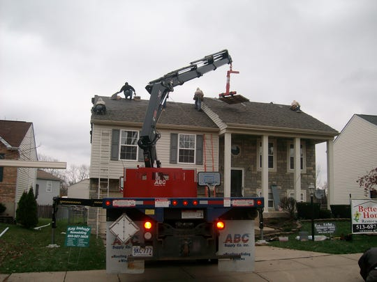 Workers fix the roof at home in Hebron, Kentucky, which was damaged by a windstorm caused by the remnants of Hurricane Ike in 2008.