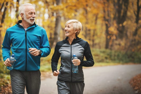 Senior Couple Jogging In A Forest