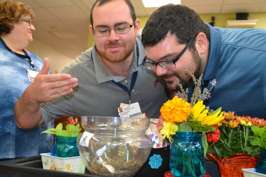Alexander Kettles, masters of Counseling Services,  and Kyle DePaul , therapist look at plants during Laura DePrado's recent horticultural therapy program at Carrier Clinic in Montgomery.